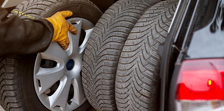 Mécanicien automobile masculin changeant le pneu dans le garage