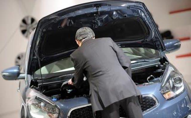 L'homme inspecte le moteur d'une voiture KIA