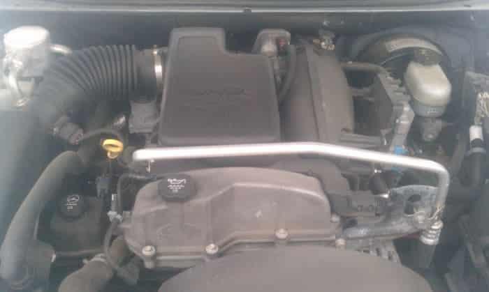 Bajo el capó del Chevy.  El filtro de aire está a la izquierda, junto a la imagen conectada al tubo de plástico.  El cuerpo del acelerador está en la parte superior central, detrás de la gran carcasa de plástico.