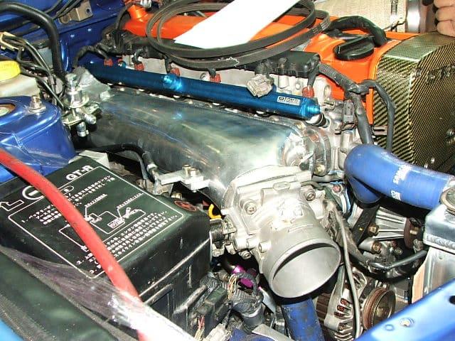 Un colector de admisión de la serie NOZZS RB instalado en un RB26.  La tubería de salida de agua limpia el colector.  Para aquellos que usan baterías más grandes, es posible que necesite una reubicación de la batería o una batería más pequeña.