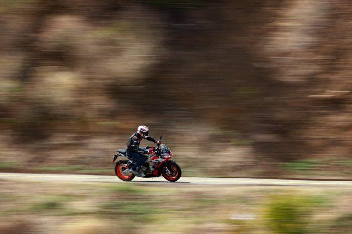 Plano lateral de Aprilia Tuono 660 cabalgando por una carretera de montaña
