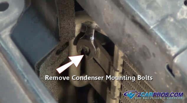 Retirar los tornillos de fijación del condensador.